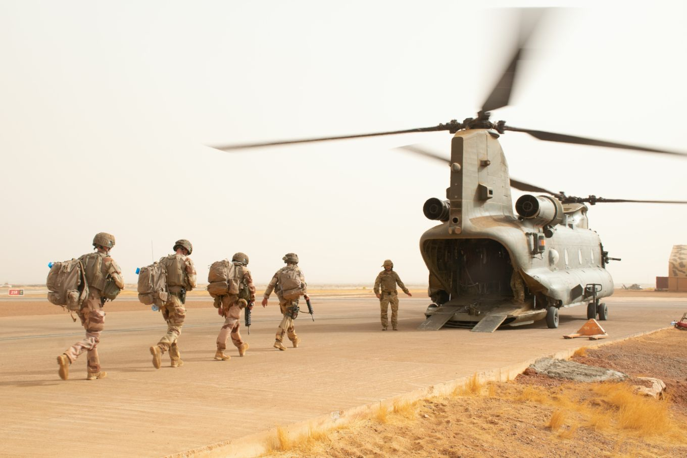 French troops walk towards an RAF Chinook.